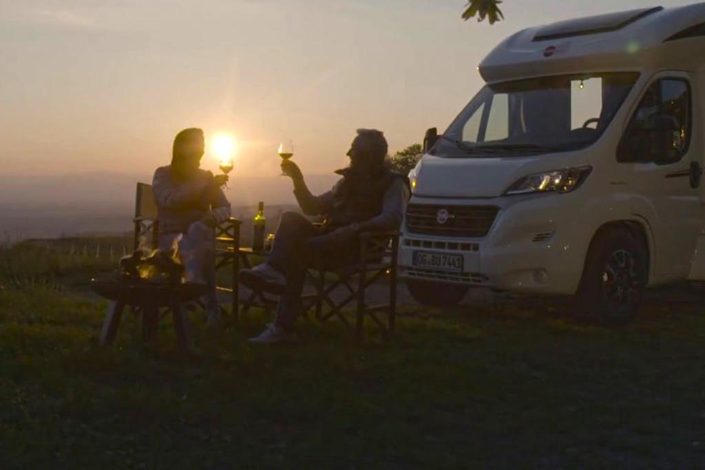 El placer de un nómada moderno, Autocaravana, vino y atardecer